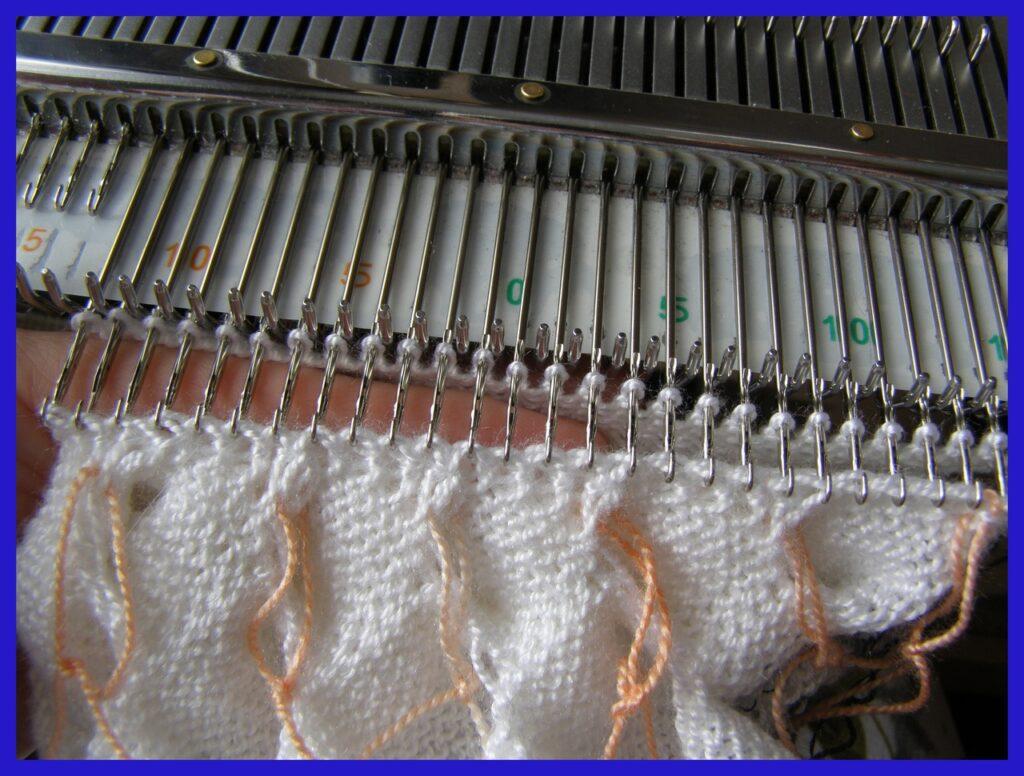 Навешивание звеньев кромочного края декоративной детали на иглы после вязания околыша